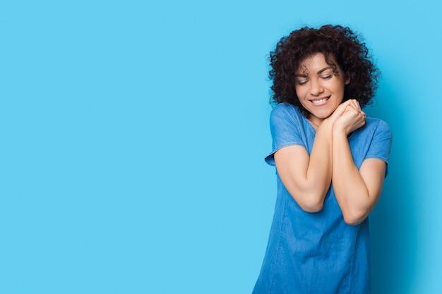 De aanbiddelijke vrouw stelt op een blauwe studiomuur gebaren genoegen en glimlacht dichtbij vrije ruimte