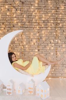 De aanbiddelijke zwangere vrouw in gele kleding ligt op een maan vóór een muur