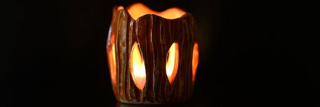 De aangestoken kaars brandt in de kandelaar op een zwarte achtergrond. prachtig vuurlicht uit de spleten van een kandelaar gemaakt van klei. banner