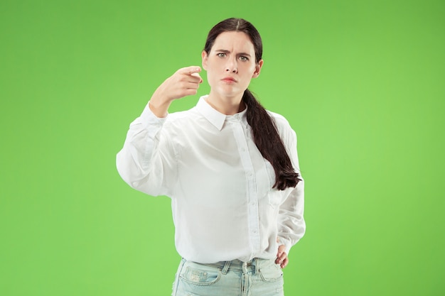 De aanmatigende bedrijfsvrouw wijst u en wil u, het portret van de halve lengteclose-up op groene achtergrond.