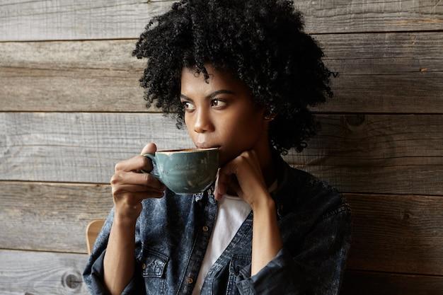 De aantrekkelijke afro-amerikaanse hipstervrouw kleedde stylishly nadenkend het drinken van koffie of thee uit grote kop, weg kijkend met ernstige peinzende uitdrukking, makend plannen voor dag. mensen en levensstijl