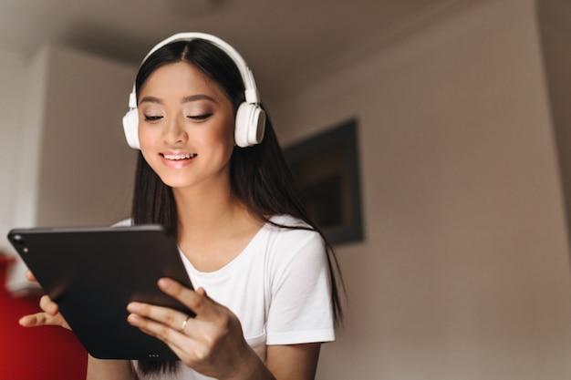 De aantrekkelijke aziatische vrouw met glimlach onderzoekt tablet