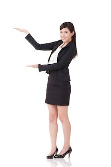 De aantrekkelijke bedrijfsvrouw introduceert met hand, volledig lengteportret op witte achtergrond.