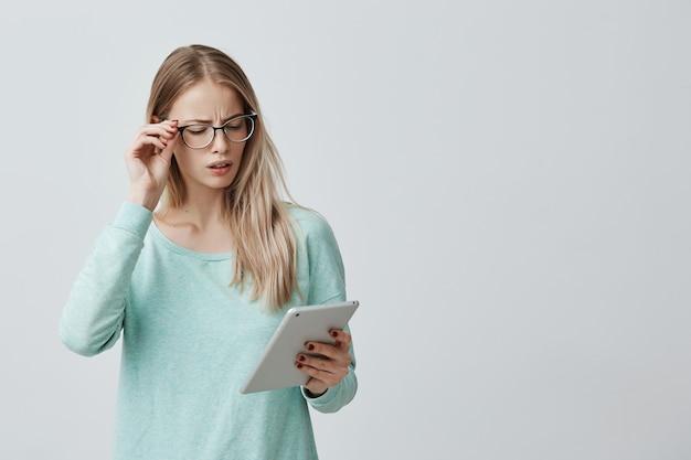 De aantrekkelijke blondebeambte in eyewear werkt met digitale tablet