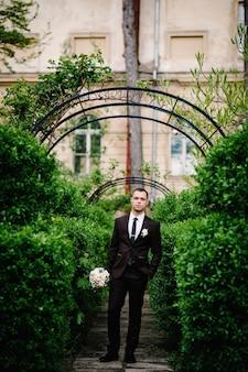 De aantrekkelijke bruidegom in een pak en stropdas met bruidsboeketbloemen en een corsages of knoopsgat op het jasje staat op de achtergrondboog met groen in het park.