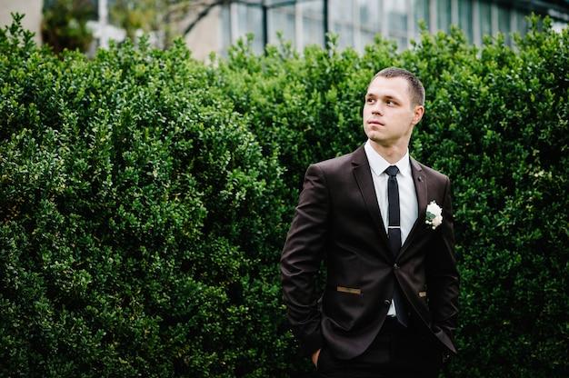 De aantrekkelijke bruidegom in een pak en stropdas met corsages of knoopsgat op de jas, staat op de achtergrond groen in de tuin, park. natuur.