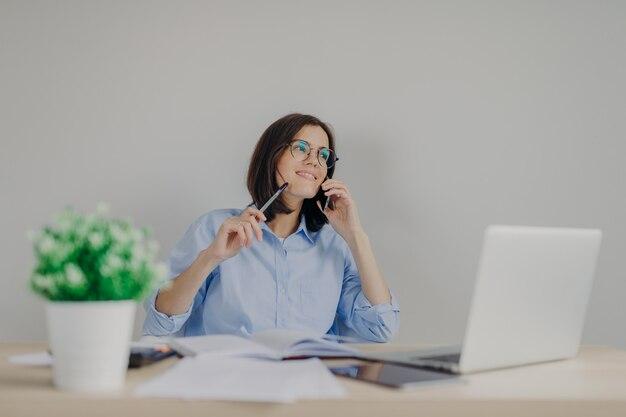 De aantrekkelijke donkerbruine vrouwelijke journalist schikt vergadering via celtelefoon, werkt aan nieuw artikel op laptop computer