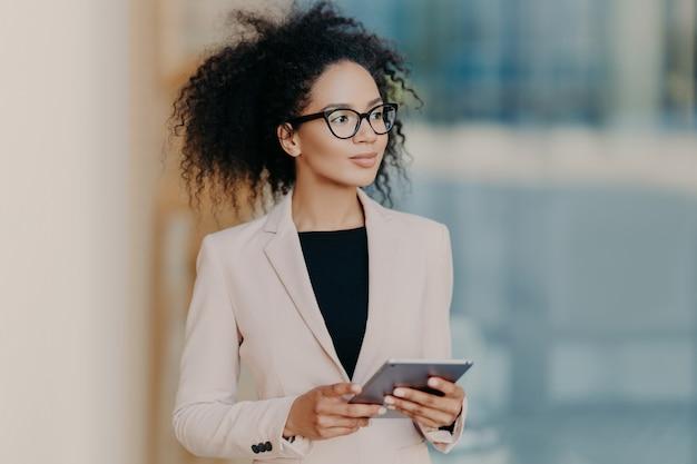De aantrekkelijke elegante donkere gevilde onderneemster gebruikt digitale tablet, gekleed in formele slijtage, bevindt zich in bureau