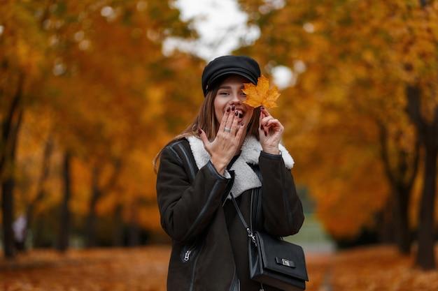 De aantrekkelijke gelukkige jonge vrouw in modieuze kleding houdt een geel esdoornblad dichtbij gezicht en behandelt mond met hand. grappig mooi meisje loopt in het herfstpark op een achtergrond van gouden gebladerte.