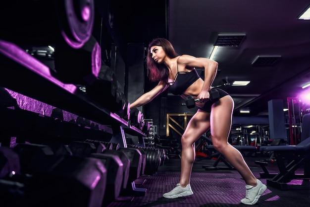 De aantrekkelijke geschikte sexy vrouw in de gymnastiek buigt met een barbell. vrouw training terug