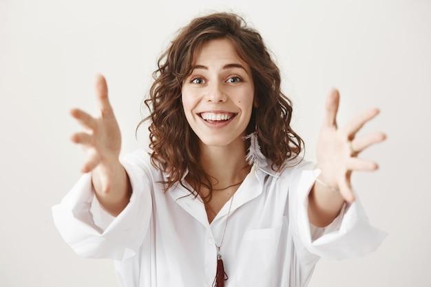 De aantrekkelijke glimlachende vrouw breidt handen uit, bereikt of omhelst iemand