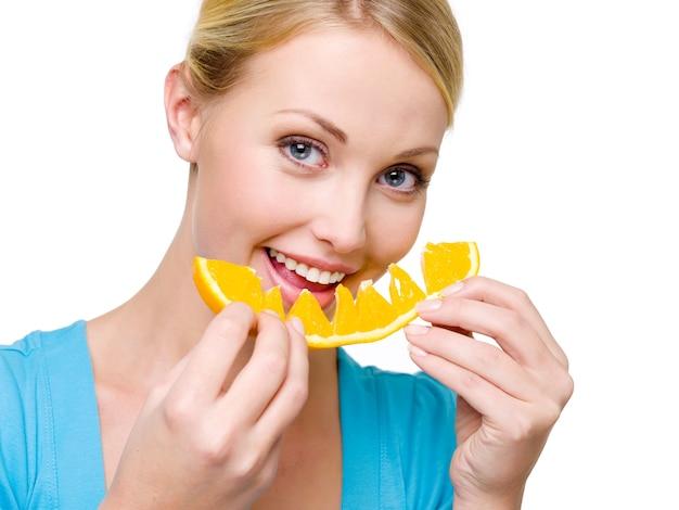 De aantrekkelijke glimlachende vrouw eet de verse sinaasappel - over witte ruimte