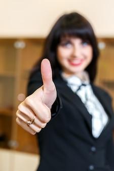 De aantrekkelijke glimlachende vrouw in bureau toont duim, ficussen op een vinger