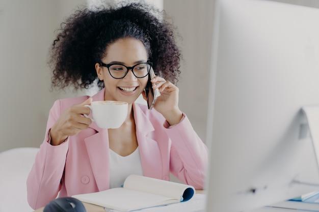 De aantrekkelijke glimlachende vrouwelijke ondernemer geniet van aromatische drank, houdt witte mok drank