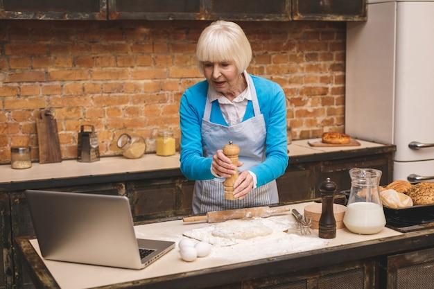 De aantrekkelijke hogere oude vrouw kookt op keuken. grootmoeder lekker bakken maken. laptop gebruiken.