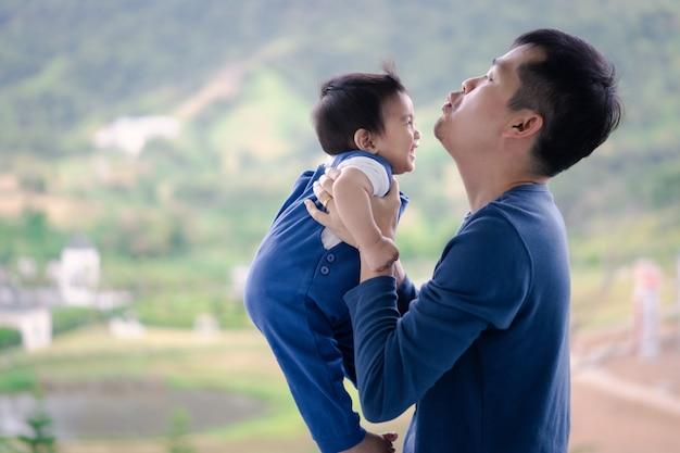 De aantrekkelijke jonge aziatische vader houdt en speelt samen met zijn kleine babyjongen bij het balkon in de ochtendtijd.