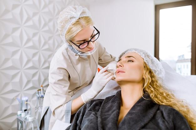 De aantrekkelijke jonge blonde vrouw krijgt verjongende gezichtsinjecties bij moderne cosmetologiekliniek. jonge vrouwelijke deskundige schoonheidsspecialiste vult vrouwelijke rimpels met hyaluronzuur