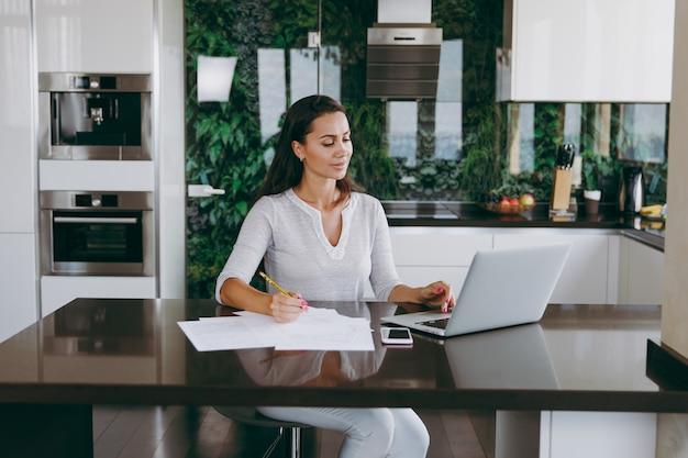 De aantrekkelijke jonge moderne zakenvrouw die thuis met documenten en laptop in de keuken werkt