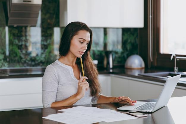 De aantrekkelijke jonge peinzende zakenvrouw die thuis met documenten en laptop in de keuken werkt