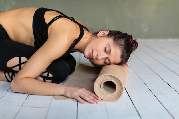 De aantrekkelijke jonge vrouw legde haar hoofd bij gevouwen yoga of geschiktheidsmat na oefenrekoefening bij yogales