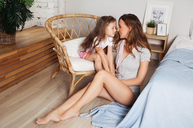 De aantrekkelijke jonge vrouw met weinig leuk meisje brengt thuis tijd samen door. gelukkig familie concept. moeder en klein kind kussen en knuffelen