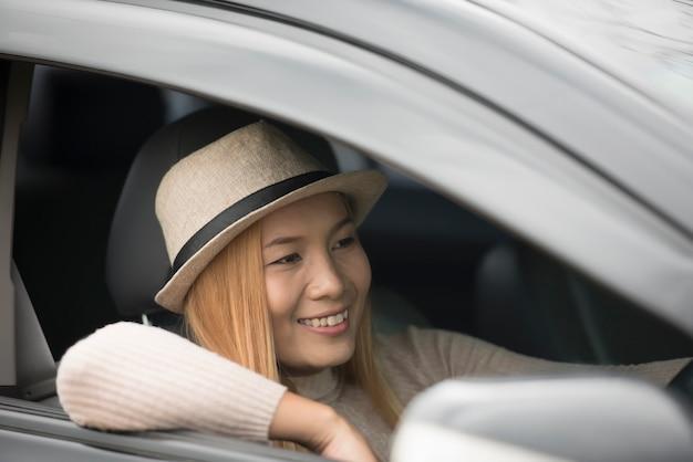 De aantrekkelijke jonge vrouwenzitting in de auto opent het venster geniet van aard.