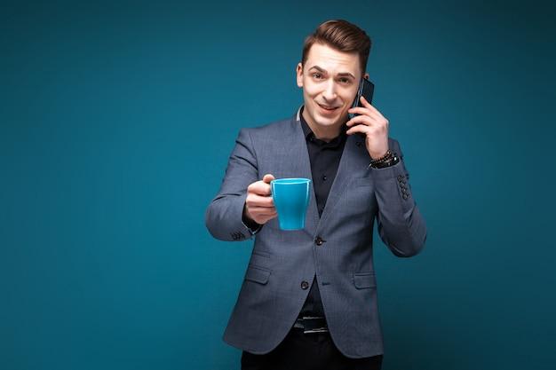 De aantrekkelijke jonge zakenman in grijs jasje en het zwarte overhemd houden blauwe kop en spreken op de telefoon
