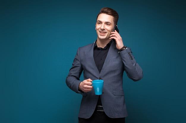 De aantrekkelijke jonge zakenman in grijs jasje en zwart overhemd houdt blauwe kop en spreekt op de telefoon