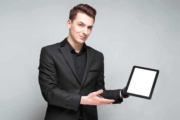 De aantrekkelijke jonge zakenman in zwart jasje, duur horloge en zwart overhemd houdt lege tablet