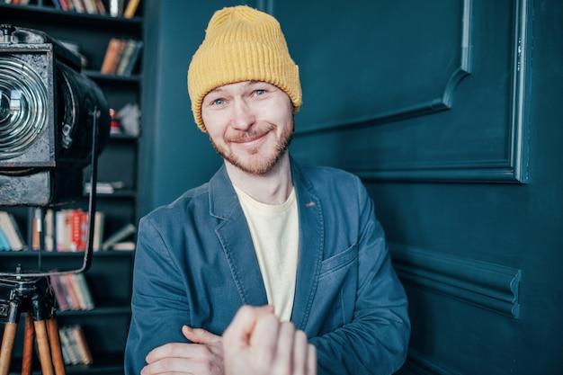 De aantrekkelijke kale glimlachende mens hipster met baard in gele hoed toont onfatsoenlijke gebaarvuist