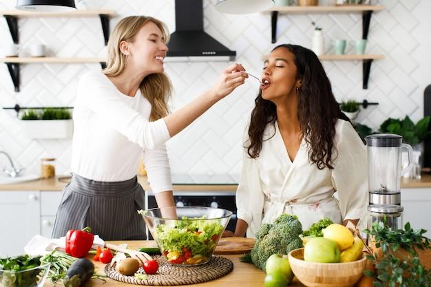 De aantrekkelijke kaukasische vrouw voedt mooie mulatvrouw met verse salade op modern ontworpen keuken