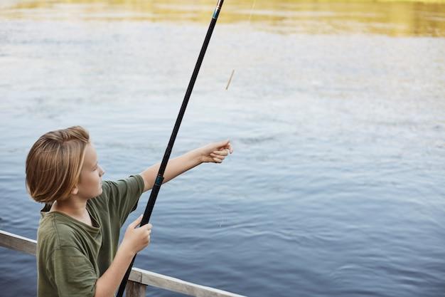 De aantrekkelijke kleine kerel die hengel gieten aan rivier, wil grote vissen vangen, weekend doorbrengen op aard, dichtbij rivier of meer, zeer geconcentreerd zijn.