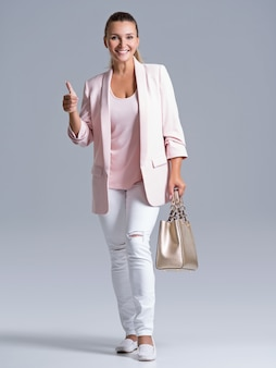 De aantrekkelijke lachende vrouw houdt de gouden handtas.