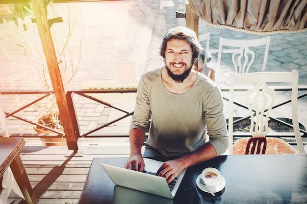 De aantrekkelijke mannelijke arbeider gebruikt computer in cafetaria