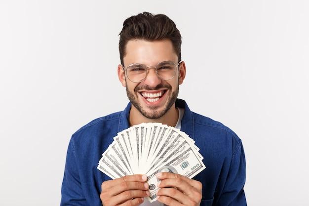 De aantrekkelijke mens houdt contant geldgeld in één hand, op geïsoleerd wit