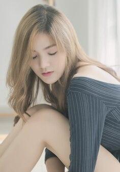 De aantrekkelijke mooie aziatische vrouw sluit haar ogen en zittend op bed
