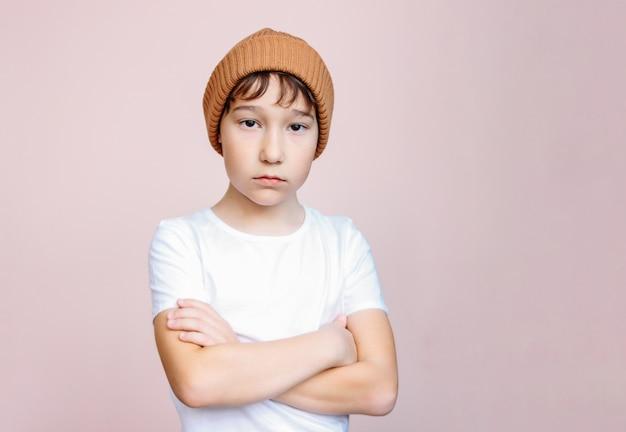 De aantrekkelijke tween ongelukkige die jongen met donker haar in hoed bekijkt camera op lichtrose wordt geïsoleerd