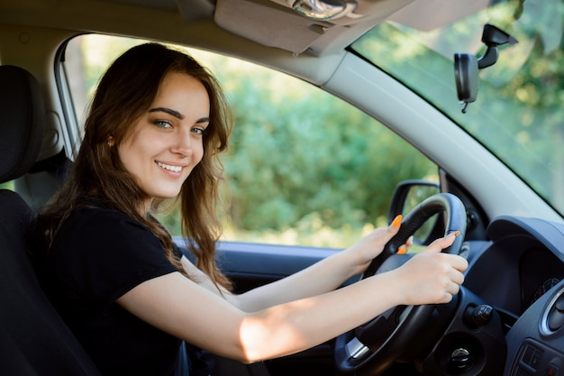 De aantrekkelijke vrolijke meisjesbestuurder zit in de bestuurdersstoel van een moderne auto