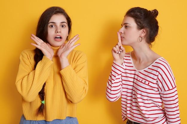De aantrekkelijke vrouw die gestreept overhemd draagt houdt vinger dichtbij lippen terwijl het vertellen van geheim aan haar vriend