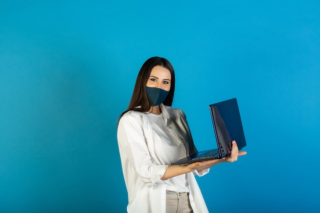 De aantrekkelijke vrouw die gezichtsmasker draagt, gebruikt laptop die op blauw wordt geïsoleerd
