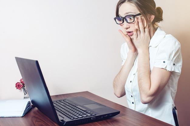 De aantrekkelijke vrouw die op kantoor met laptop werkt grijpt zijn hoofd