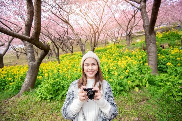 De aantrekkelijke vrouw geniet van met cherry blossom in het park