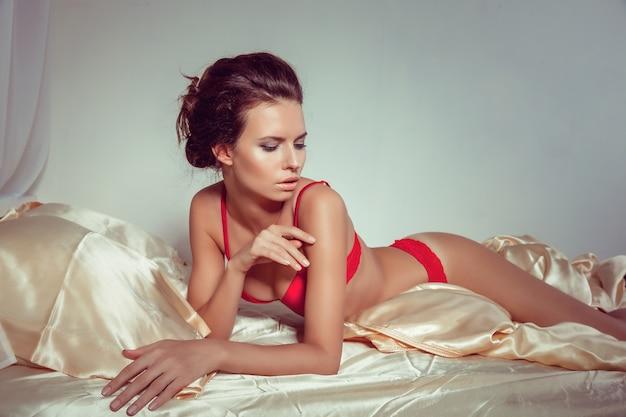 De aantrekkelijke vrouw in sexy rode lingerie die in verleidelijk liggen stelt op bed