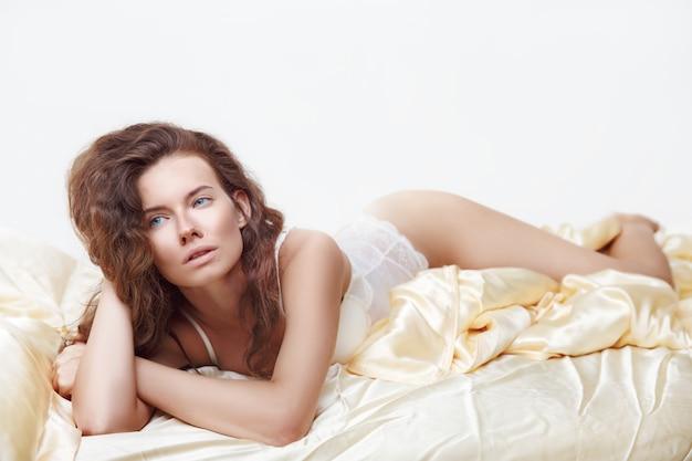 De aantrekkelijke vrouw in sexy witte lingerie die in verleidelijk liggen stelt op bed