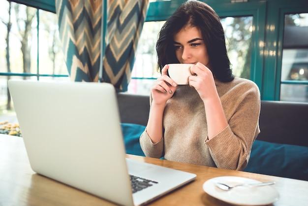 De aantrekkelijke vrouw met een laptop drinkt een kopje koffie in het café