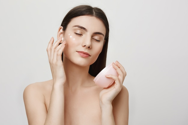 De aantrekkelijke vrouw past gezichtscrème, anti-verouderingsproduct toe