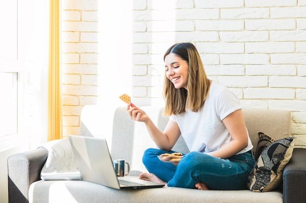 De aantrekkelijke vrouw thuis op bank die op tv letten toont en wafels eet