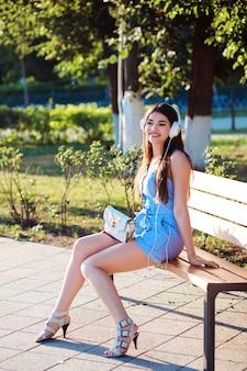 De aantrekkelijke vrouw zit op de bank in het park en luistert aan muziek.