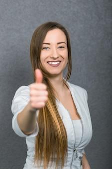 De aantrekkelijke vrouwelijke artsenvrouw toont duimen