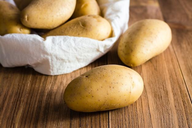 De aardappelen op de zak aardappelen op een houten tafel